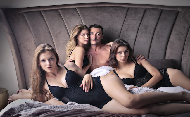 guy in bed with 3 girls