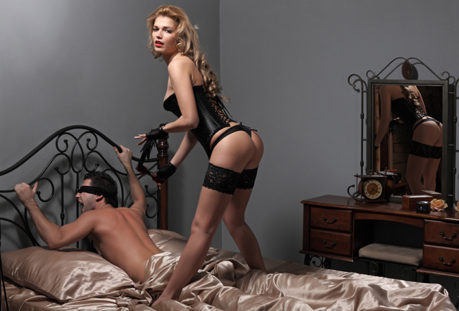 Young man and the woman are engaged BDSM in sex on a bed